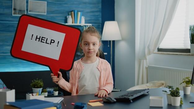 Маленький ребенок держит речевой пузырь для помощи с домашним заданием