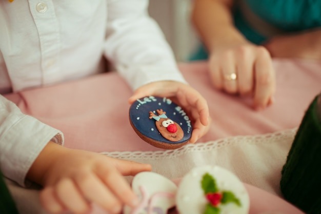 Little child holds cookie with lettering 'let it snow'