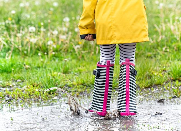 明るい黄色のレインコートと縞模様のゴム長靴を履いた小さな子供。