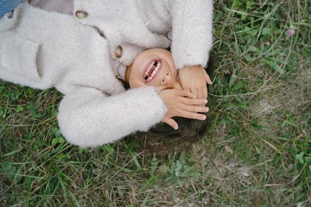 귀여운 흰색 스웨터에 작은 아이. 소녀는 공원에서 시간을 보내고