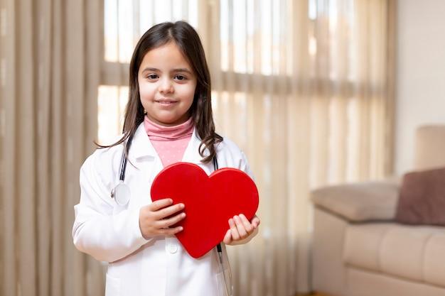 彼女の手に笑顔の大きな心を持っている医者の制服を着た小さな子供