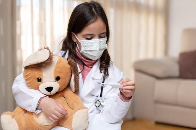 テディベアの体温を測る医者の制服を着た小さな子供。彼女は家にいます
