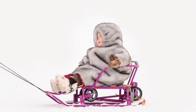 Маленький ребенок в шубе на слидах. праздник дня северного оленя народов севера.
