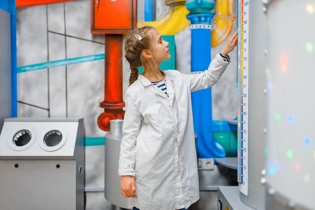 Маленький ребенок в униформе, играя доктора в лаборатории