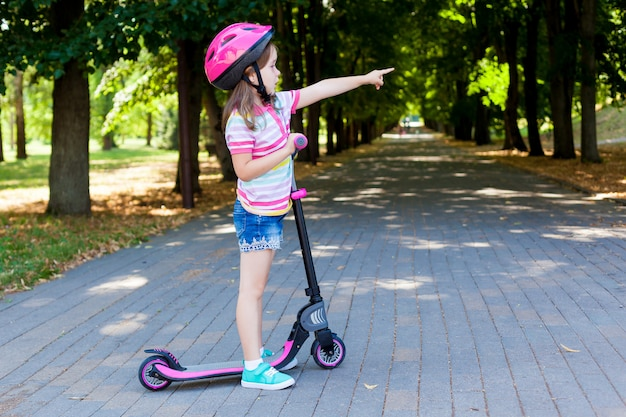Little child learning to ride a scooter in a city park on sunny summer evening.