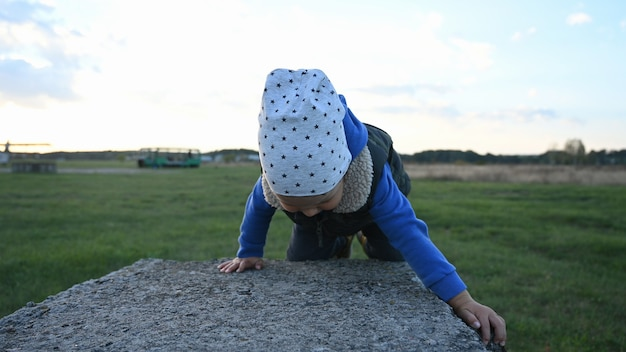 Little child learns to climb an obstacle.