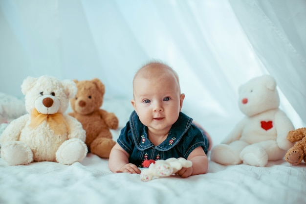Little child lies among toy bears on bed