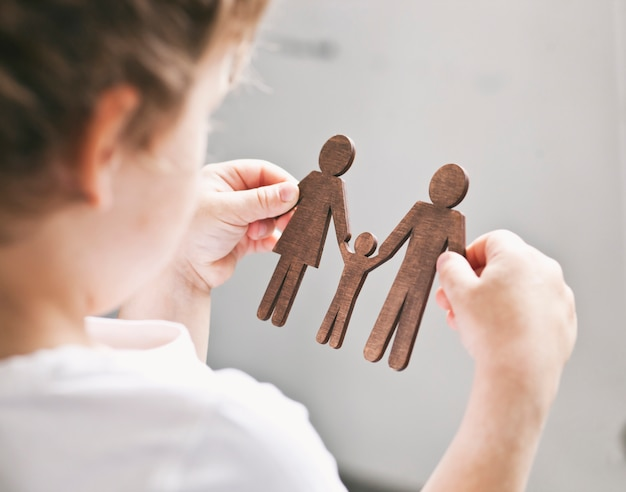 Little child looking on wooden figures of mom, dad and child in his hands. concept of child dreaming about family