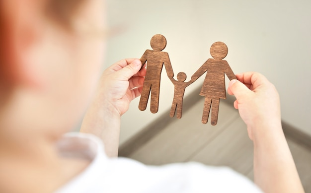 Little child looking on wooden figures of mom, dad and child in his hands.