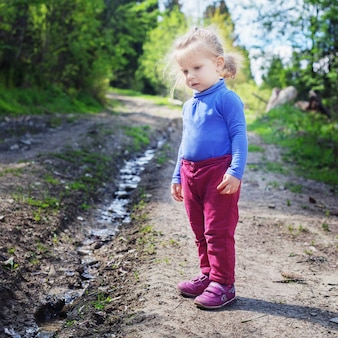 Little child looks at the creek in the woods.