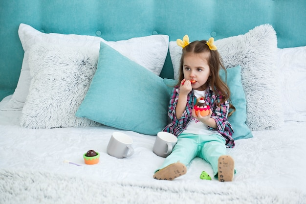 Little child looks funny eating cupcake on the bed