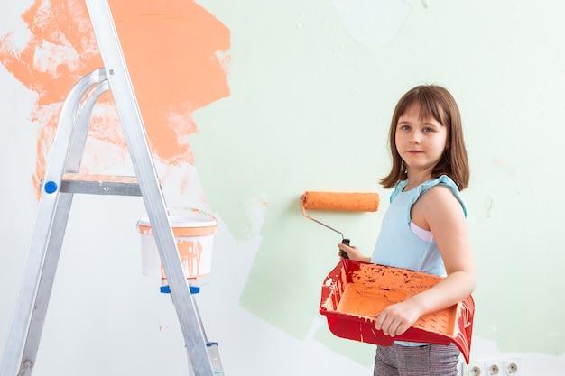 Художник маленький ребенок делает ремонт стены. косметический ремонт, ремонт и концепция перекраски.