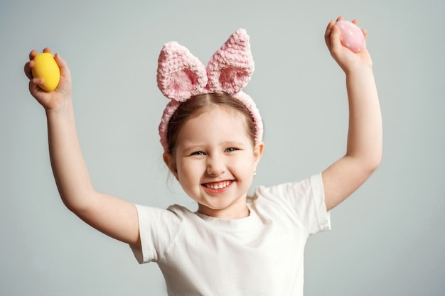 Little child in pink bunny ears headband holding easter eggs.