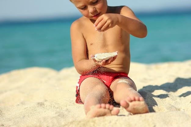 小さな子供がビーチの海岸で遊ぶ