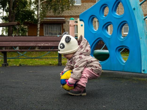 가을날 놀이터에서 공을 가지고 노는 어린 아이