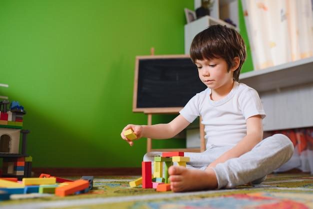 Маленький ребенок играет с множеством красочных пластиковых игрушек дома