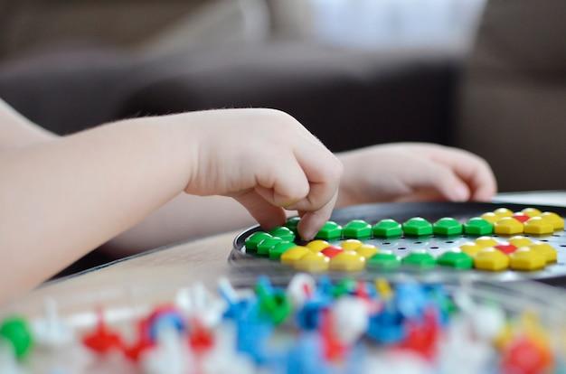 Маленький ребенок играет с мозаикой