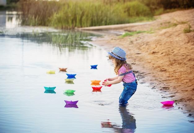 강에 종이 보트를 가지고 노는 어린 아이