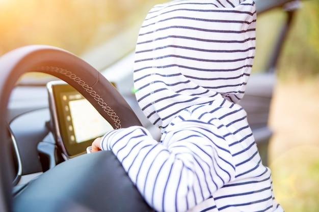어린 아이가 현대 자동차의 운전대에서 놀고 있습니다. 얼굴이 없는 클로즈업. 프리미엄 자동차의 내부입니다. 젊은 드라이버 개념
