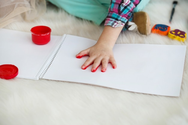 Little child raises her palm painted in red