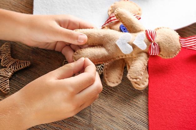 테이블에서 펠트에서 크리스마스 장난감을 바느질하는 어린 아이