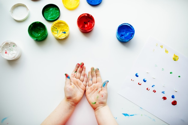 Little child shows his hands stained with paint at the table with art supplies, top view