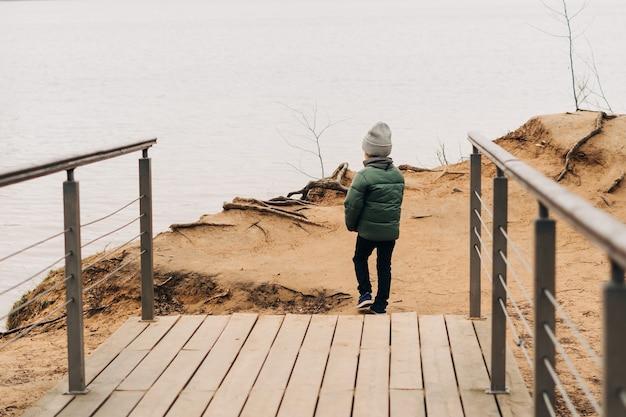 Маленький ребенок сидит на берегу озера и играет с водой, счастливый мальчик, играющий и имеющий