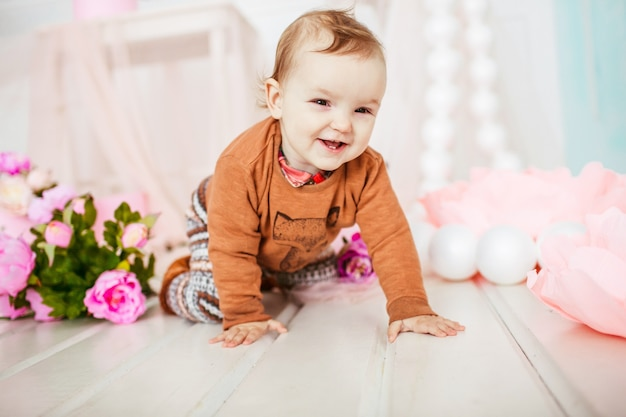 Little child sits among pink flowers on the floor