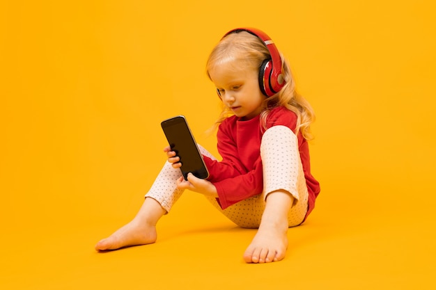 Little child sits on the floor in headphones and sits on the phone on an orange wall