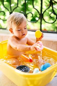 어린 아이는 물동이에 앉아서 장난감을 가지고 노는다