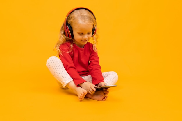 Маленький ребенок сидит на полу в наушниках и сидит на телефоне на желтом фоне