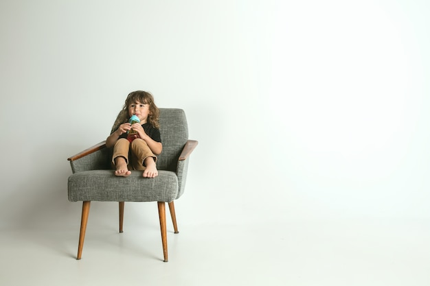 Маленький ребенок сидит и играет в кресле, изолированном на белом пространстве. молодой мальчик со светлыми волосами выглядит заинтересованным миром, окружающим его