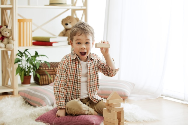 Little child sitting on the floor. pretty smiling surprised boy palying with wooden cubes at home.