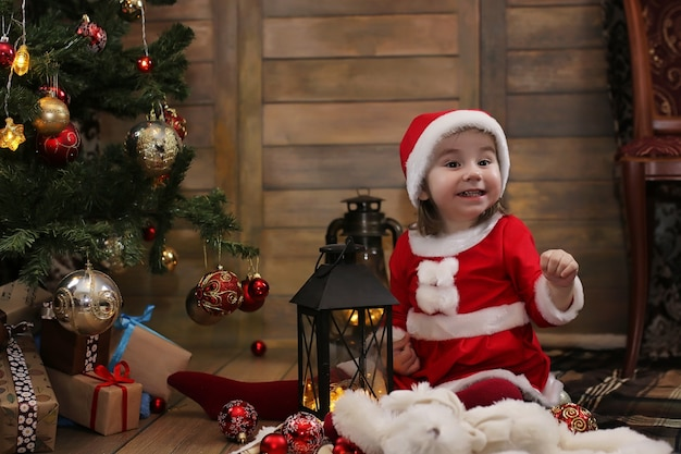 Little child sitting in front of a christmas tree and playing with toys