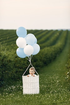 Маленький ребенок сидит в корзине с воздушными шарами