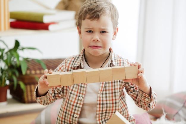 집에서 나무 큐브를 가지고 노는 바닥에 앉아 어린 아이