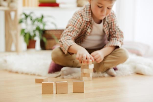 床に座っている小さな子供。家で木製の立方体でパリーをしているかわいい男の子。コピーまたはネガティブスペースとテキストのモックアップを含む概念的なイメージ