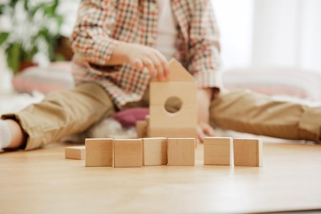 Маленький ребенок сидит на полу. симпатичный мальчик играет с деревянными кубиками дома. концептуальное изображение с копией или негативным пространством и макет для вашего текста