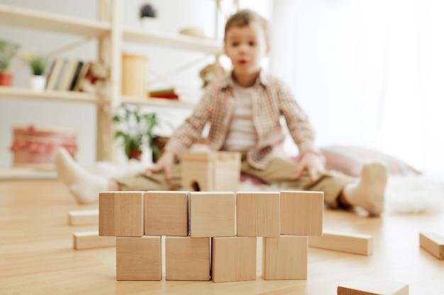 바닥에 앉아 작은 아이. 집에서 나무 조각으로 palying 예쁜 소년. 텍스트 복사 또는 네거티브 공간과 모형이있는 개념적 이미지