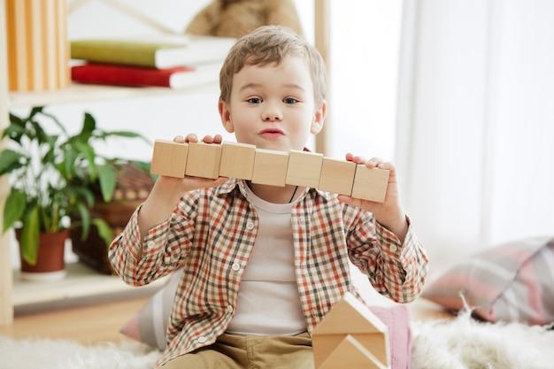 床に座っている小さな子供。家で木製の立方体を持って歩き回っているかわいい男の子。
