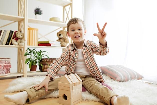 집에서 나무 큐브와 palying 바닥 예쁜 소년에 앉아 어린 아이