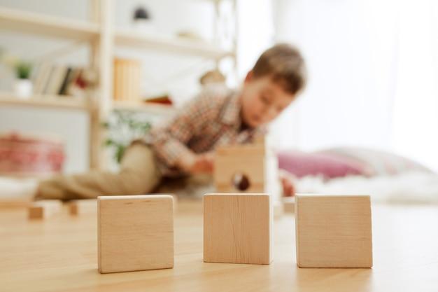 床に座っている小さな子供が家で木製の立方体でパリーしているかわいい男の子