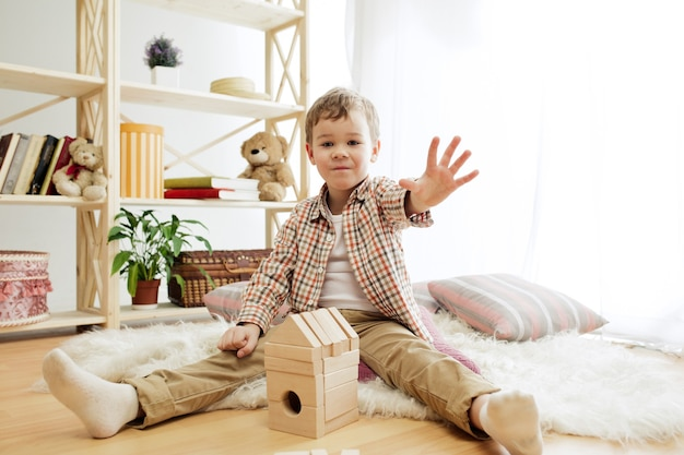 바닥에 앉아 작은 아이. 나무 큐브 집에서 노는 예쁜 소년. 복사 또는 부정적인 공간이있는 개념적 이미지