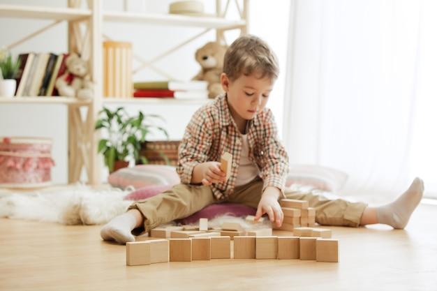 바닥에 앉아 작은 아이. 나무 큐브 집에서 노는 예쁜 소년. 복사 또는 부정적인 공간이있는 개념적 이미지 프리미엄 사진