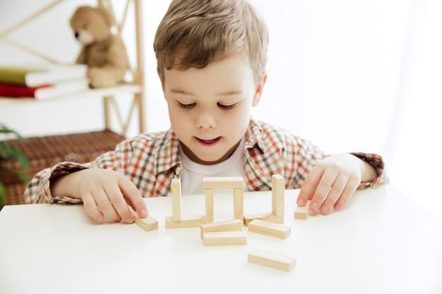 Маленький ребенок сидит на полу. симпатичный мальчик, играя с деревянными кубиками дома.