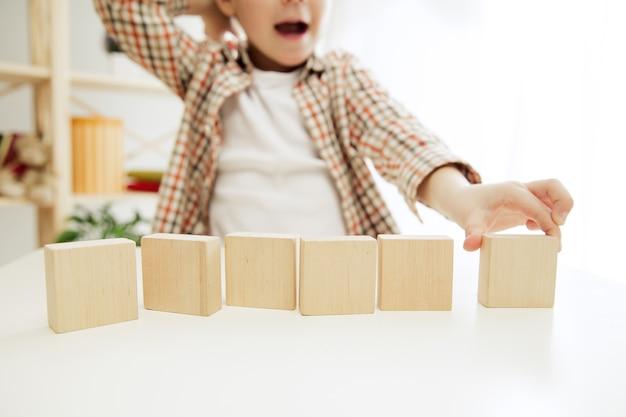 床に座っている小さな子供。家で木製の立方体で遊んでいるかわいい男の子。