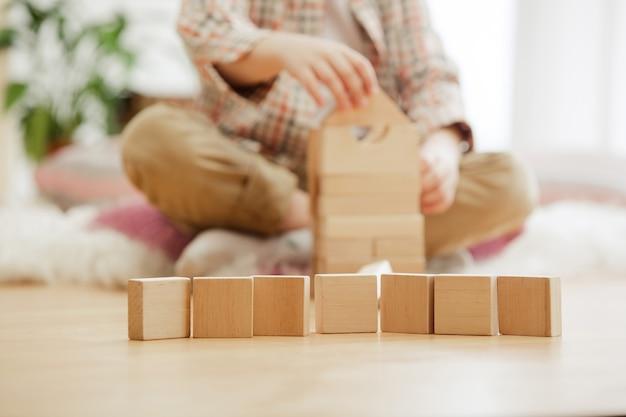 바닥에 앉아 작은 아이. 집에서 나무 큐브 가지고 노는 예쁜 소년.