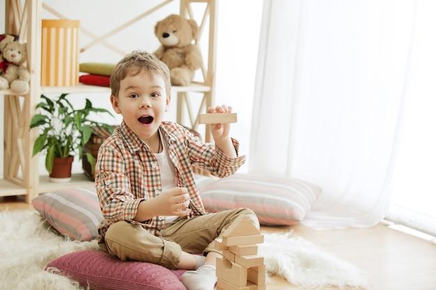 Маленький ребенок сидит на полу. довольно улыбающийся удивленный мальчик играет с деревянными кубиками дома. концептуальное изображение с копией или негативным пространством и макет для вашего текста.