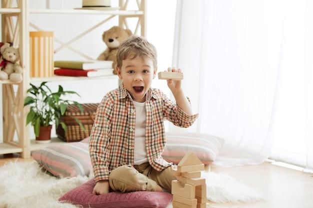 床に座っている小さな子供。家で木製の立方体を持って歩いているかなり笑顔の驚いた少年。