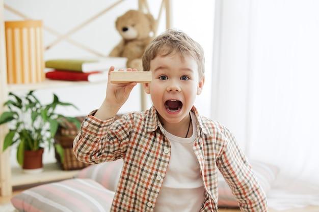 바닥에 앉아 작은 아이. 나무 큐브 집에서 놀고 꽤 웃는 놀된 소년. 복사 또는 음수 공간이있는 개념적 이미지. 프리미엄 사진